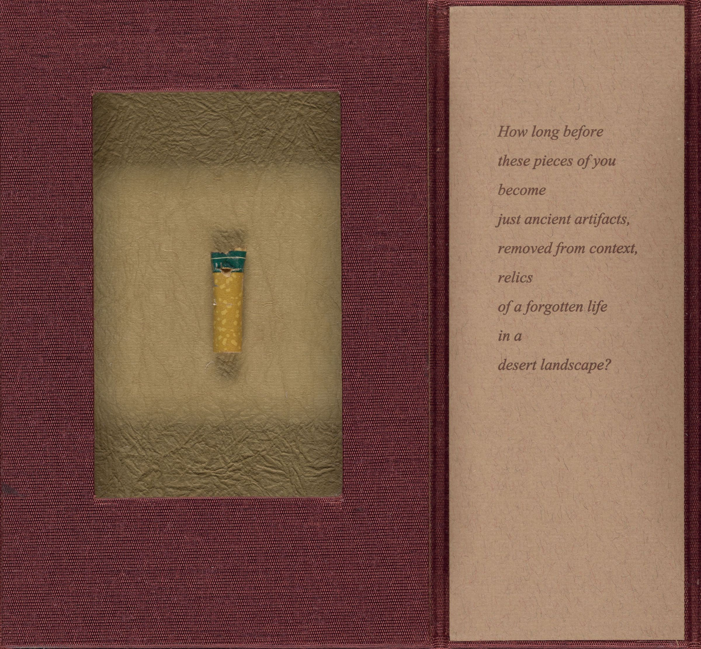 Photo of dark red artist book featuring cigarette butt and text on tan paper